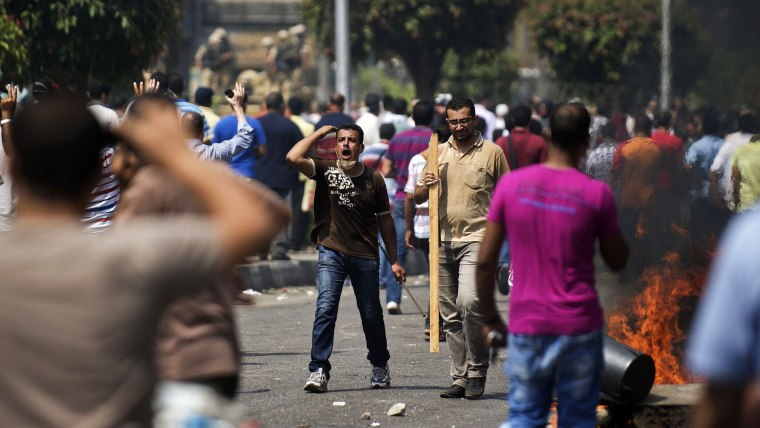 Supporters of ousted president Mohamed Morsi clash with Egyptian riot police on a street leading to Rabaa al-Adawiya square in Cairo on August 14, 2013 as security forces backed by bulldozers moved in on two huge pro-Morsi protest camps, launching a...
