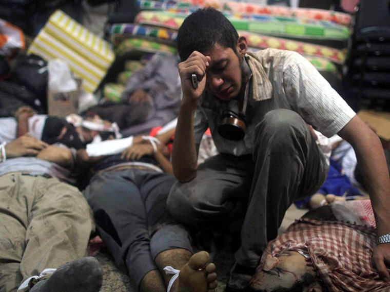 A young man mourns next to the bodies of protesters killed during the clearing of one of the two sit-ins of ousted president Morsi supporters, at the field hospital, near Rabaa Adawiya mosque, in Cairo, Egypt, on August 14, 2013. (Photo by Mosaab...