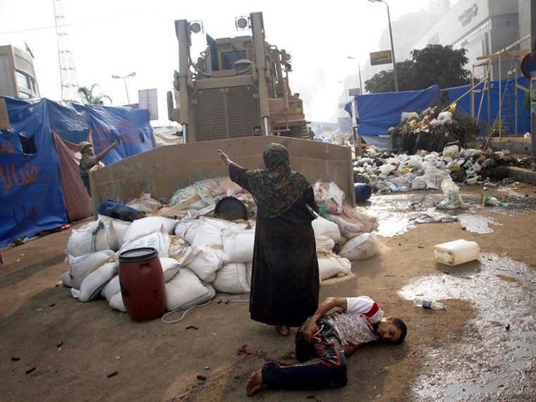 An Egyptian woman tries to stop a military bulldozer from hurting a wounded youth during clashes that broke out as Egyptian security forces moved in to disperse supporters of Egypt's deposed president Mohamed Morsi in a huge protest camp near Rabaa al...