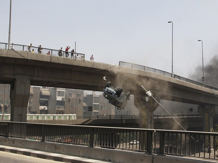 A police vehicle is pushed off of the 6th of October bridge by protesters close to the largest sit-in by supporters of ousted Islamist President Mohammed Morsi in the eastern Nasr City district of Cairo, Egypt, Wednesday, Aug. 14, 2013.  (Photo by...