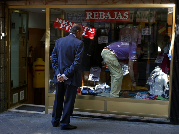 A man window shops as a worker changes the price tags of clothing items at a store in Madrid July 31, 2013. (Photo by Susana Vera/Reuters)