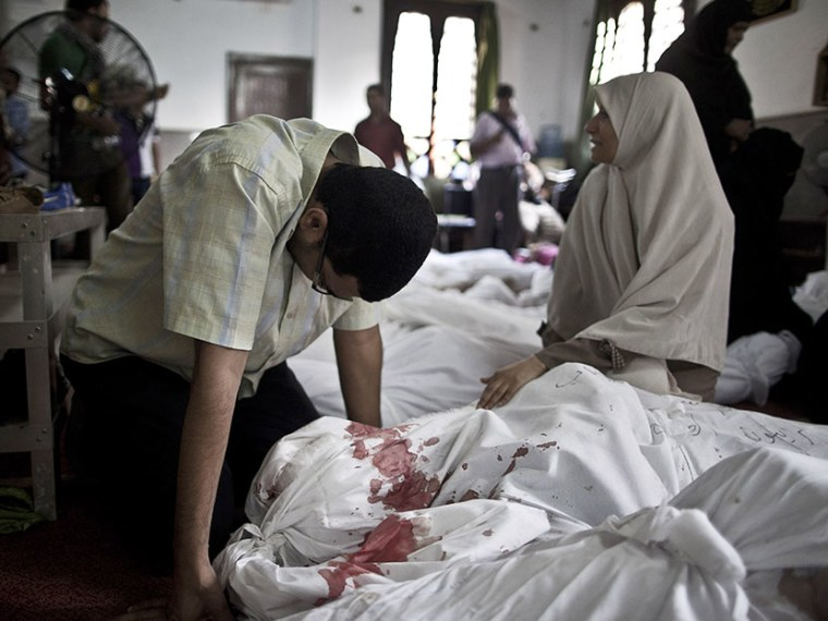Egyptians mourn over a body wrapped in shrouds at a mosque in Cairo on August 15, 2013, following a crackdown on the protest camps of supporters of ousted Islamist president Mohamed Morsi the previous day.  (Photo by Mahmoud Khaled/AFP/Getty Images)
