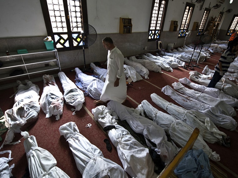 An Egyptian man walks between lines of bodies wrapped in shrouds at a mosque in Cairo on August 15, 2013, following a crackdown on the protest camps of supporters of ousted Islamist president Mohamed Morsi the previous day.  (Photo by Khaled Desouki...