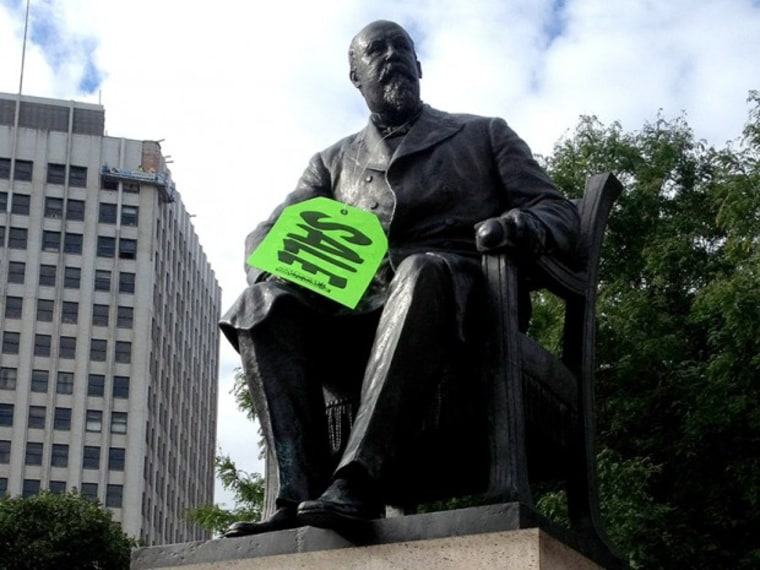 A neon green sale tag hangs on the statue of former Detroit mayor Hazen S. Pingree in Grand Circus Park in Detroit on Aug. 14, 2013. (Photo by Gary Miles/Detroit News/AP)
