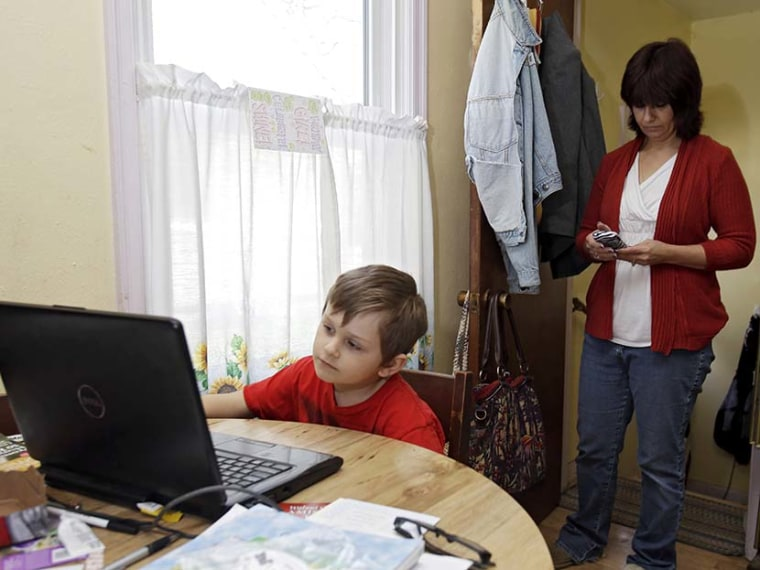 Larissa Bukowski, right, checks messages as her son David, 6, works on an online lesson in their home in Akron, Ohio. (Photo by Mark Duncan/AP)