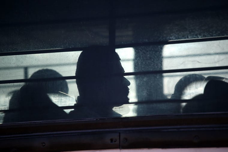 Immigration detainees from Honduras arrive by bus to board a deportation flight to San Pedro Sula, Honduras on February 28, 2013 in Mesa, Arizona. (Photo by John Moore/Getty Images)