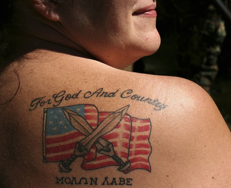 Female soldier from the 63rd battalion from Spokane, Washington, displays her tattoo during the Light Foot Militia annual gathering on Bureau of Land Management land near Priest River, Idaho June 23, 2013.  (Photo by Matt Mills/AP)