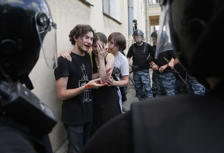 Riot police guard gay rights activists who were beaten by anti-gay protesters at an authorized gay rights rally in St. Petersburg, Russia on June 29, 2013