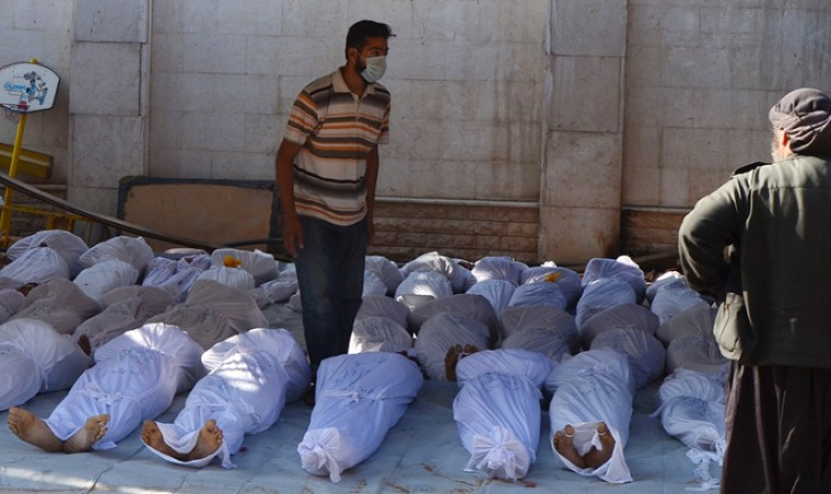 Image: Syrian activists inspect the bodies of people they say were killed by nerve gas in the Ghouta region, in the Duma neighbourhood of Damascus