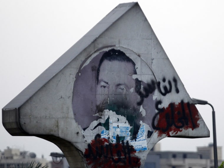 """A defaced picture of former Egyptian President Hosni Mubarak with graffiti that reads, """"Corrupt and deposed"""" along a highway in Cairo"""