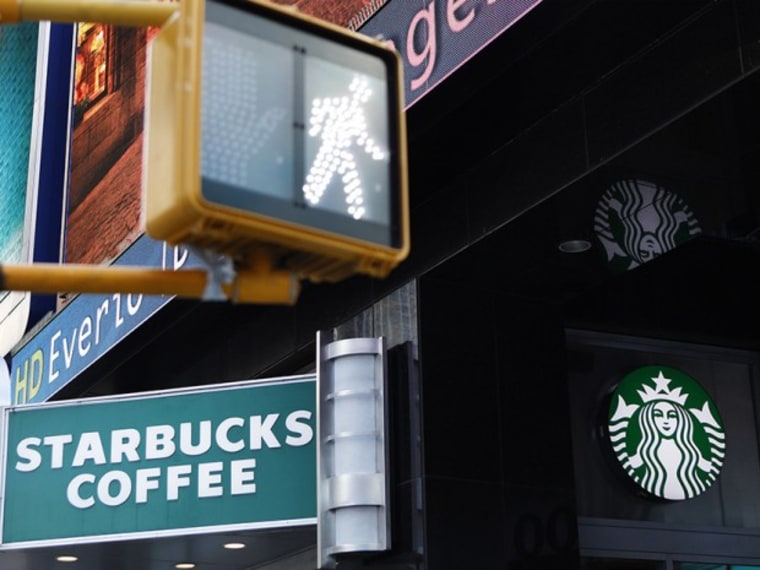 A walk sign flashes in Times Square in front of a store bearing the new Starbucks logo in New York