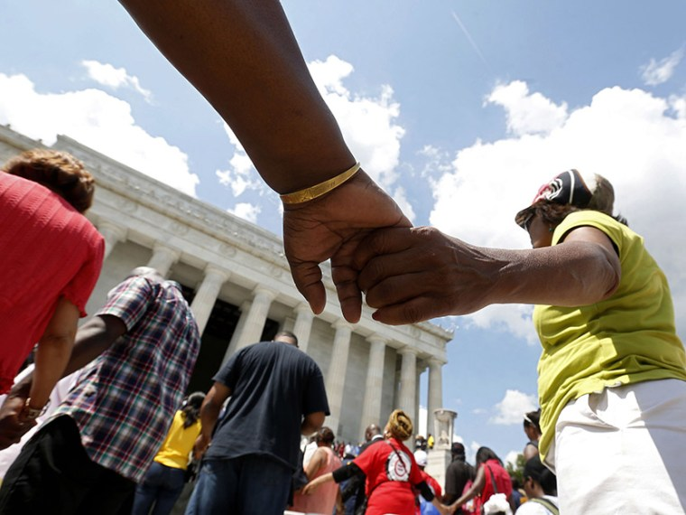Marchers hold hands in prayer at the 50th anniversary ceremony of the 1963 March ceremony at the Lincoln Memorial on Washington