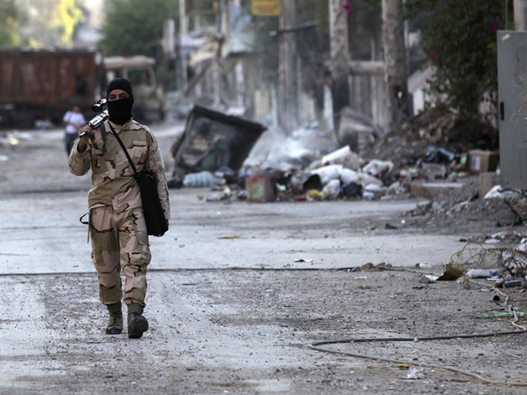 A Free Syrian Army fighter walks with his weapon on a street in Deir al-Zor