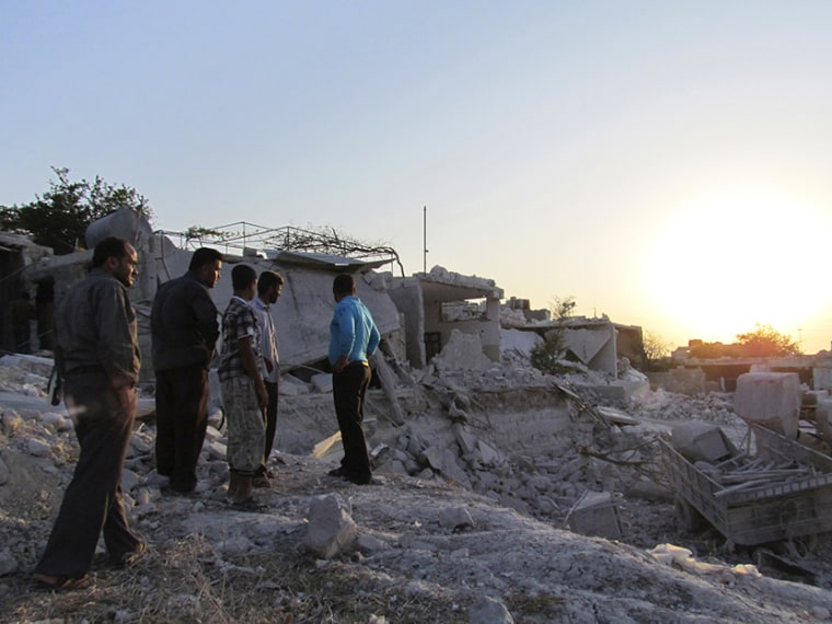 Residents inspect buildings damaged by what activists said were warplanes belonging to forces loyal to Syria's president Al-Assad in Iskat