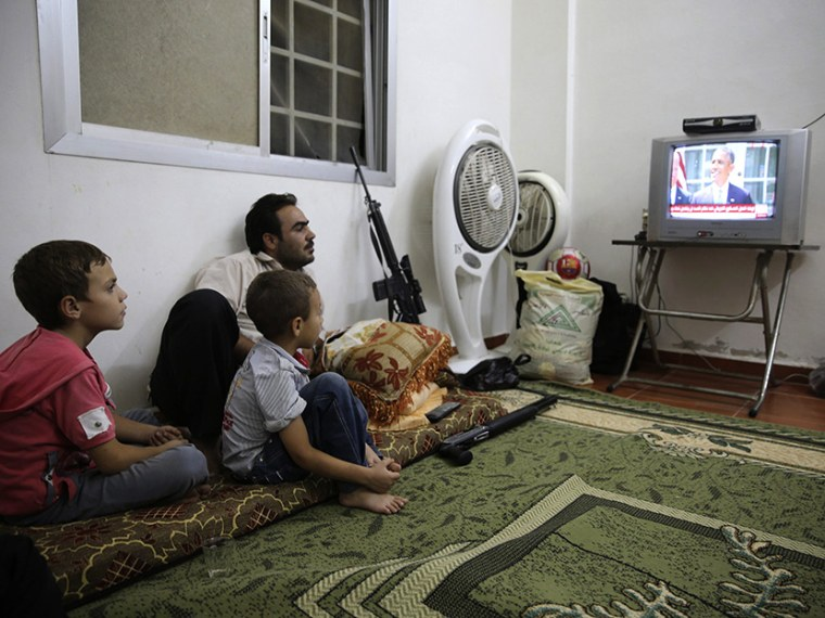 Image: A Free Syrian Army fighter watches U.S. President Barack Obama's speech with his family in Damascus
