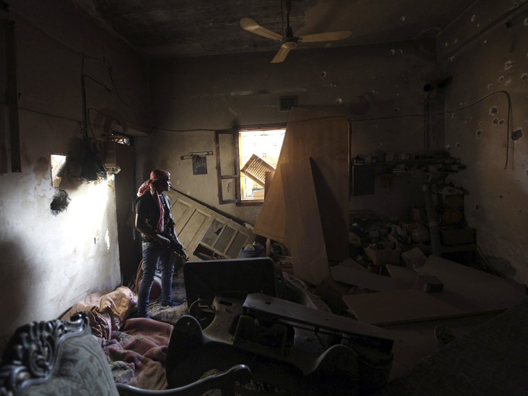 A Free Syrian Army fighter takes cover inside a damaged room in Deir al-Zor