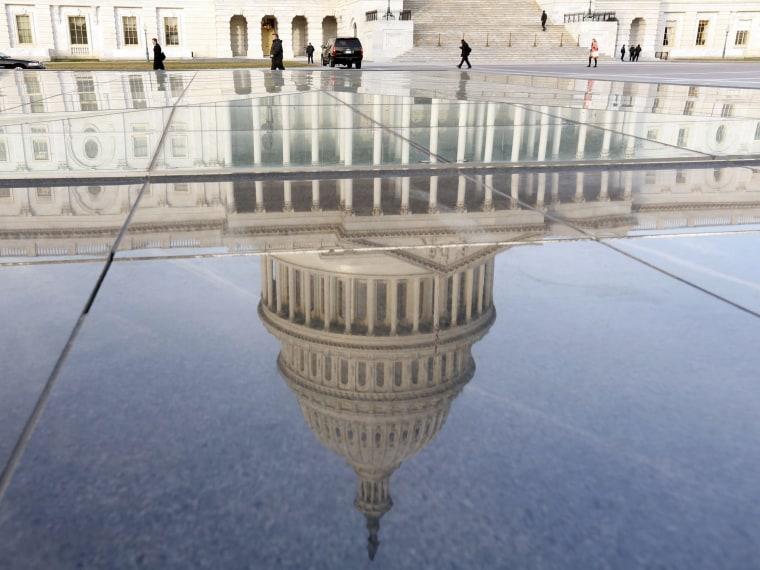 Image: The dome of the U.S. Capitol is reflected on the first day of the 113th Congress in Washington