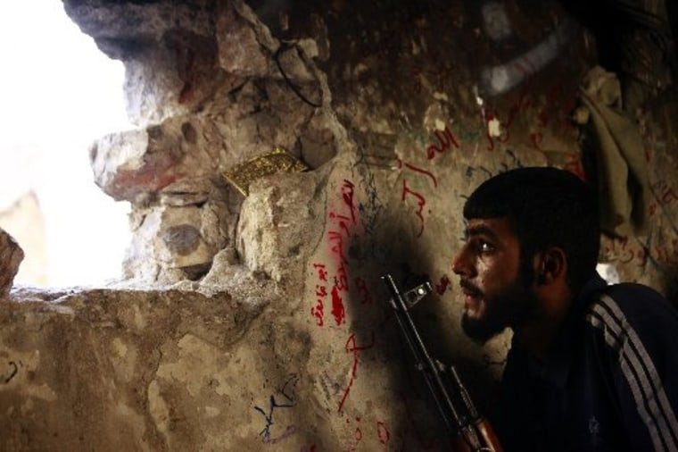 Image: A Free Syrian Army fighter sits on a lookout for forces loyal to Syrian President Bashar Al-Assad in Ogiwl