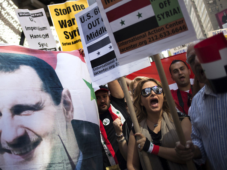 """Claudia Salmeh, a Syrian born American who supports President Bashar al-Assad, chants """"No More War,"""" as fellow activists hold an image of Assad during an anti-war rally in Times Square, New York"""