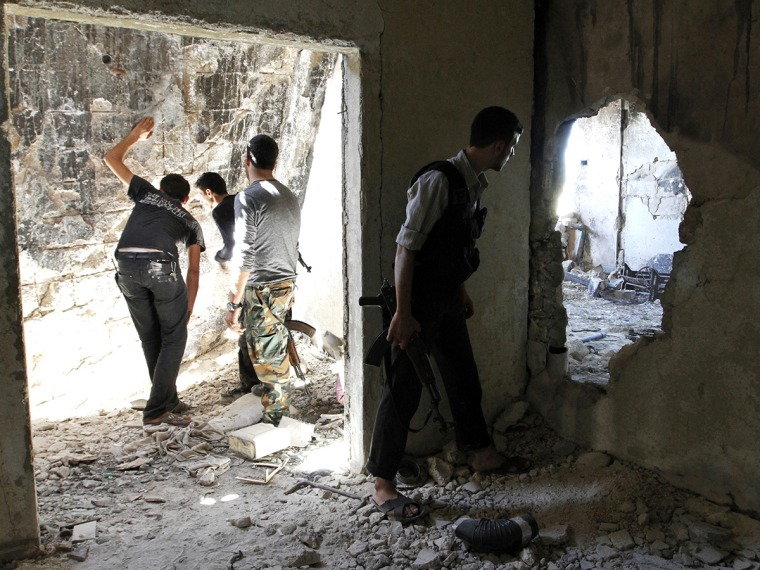 Free Syrian Army fighters peek through holes in a wall at forces loyal to Syria's President Bashar al-Assad as a fellow fighter secures the area in the old city of Aleppo