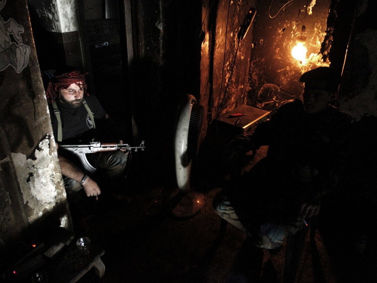 Free Syrian Army fighters smoke cigarettes as they rest in Aleppo's Qastal al-Harami neighbourhood