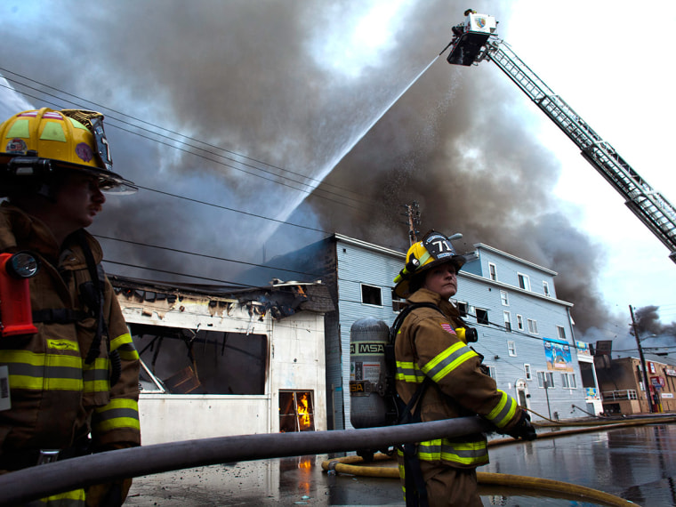 New Jersey firefighters spray water as they try to control a massive fire in Seaside Park in New Jersey