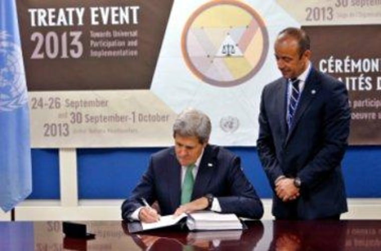 Secretary of State John Kerry signs the Arms Trade Treaty as Under Secretary-General for Legal Affairs Miguel Serpa Soares looks on.