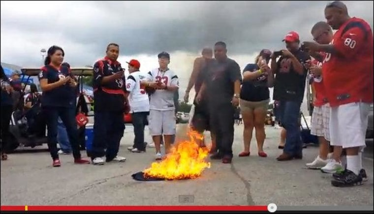 A frame from a YouTube video showing an angry football fan spend way too much money to perform a symbolic act of destruction that doesn't actually do anything about the thing he's angry about.