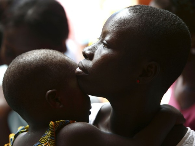 Woman and her child attend a talk on sexual and domestic violence and HIV/AIDS prevention in Lome