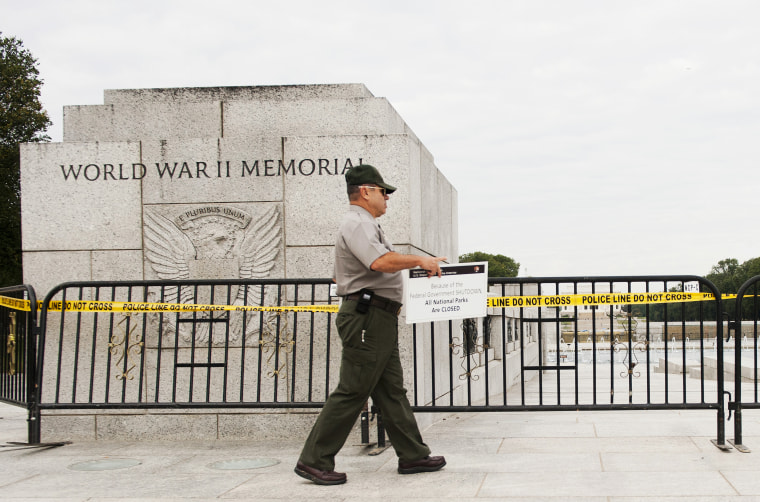 US Park Ranger Richard Trott places a closed sign on a barricade in front of the World War II Memorial monument in Washington, DC, October 1, 2013.