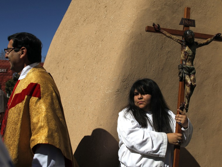 Girl carries crucifix out of the San Francisco de Asis Catholic Church after Easter Mass in Ranchos de Taos