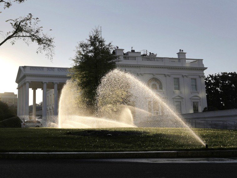 Sprinklers douse the North Lawn of the White House at sunrise in Washington