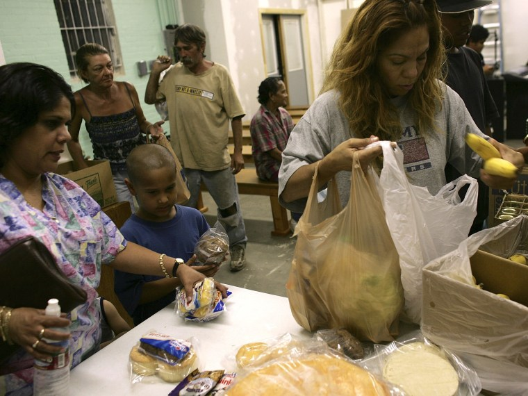 Families gather food at a food pantry for those in need inside the Streets of Destiny Church in Phoenix, Arizona.