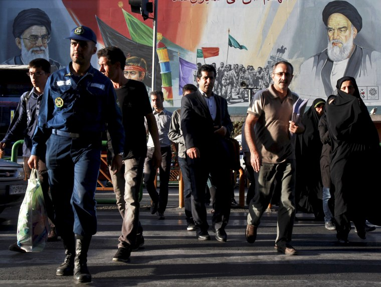 Iranians walk past a huge poster depicting Iranian soldiers during the war with Iraq in the 1980s, in Tehran.