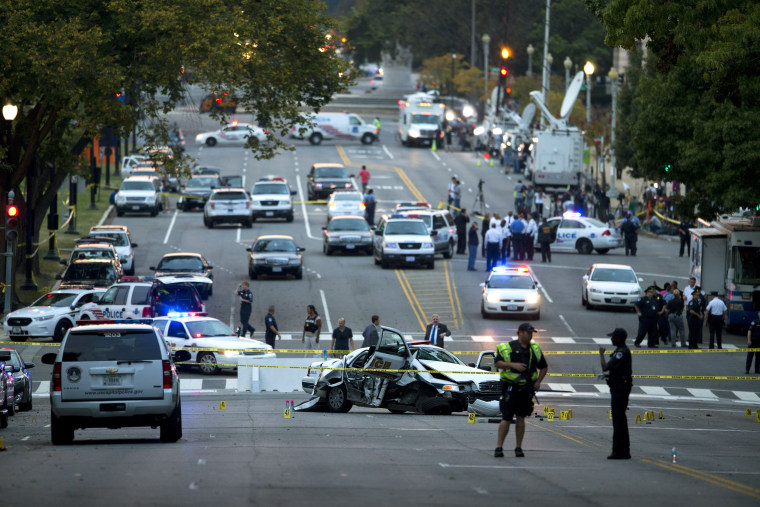 A damaged Capitol Hill police car is surrounded by crime scene tape on Constitution Avenue near the U.S. Capitol after a car chase and shooting Thursday, Oct. 3, 2013, in Washington.