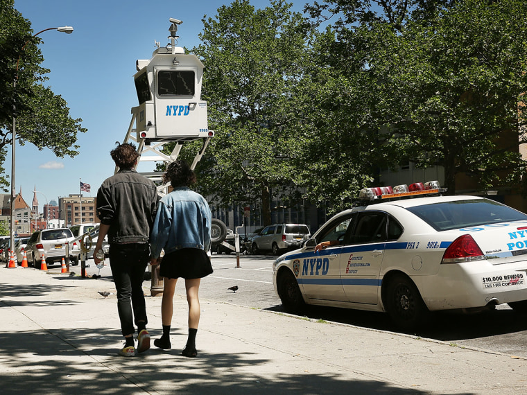 A couple walk past a police observation pod in a neighborhood with heavy crime on June 4, 2013 in the Brooklyn borough of New York City.