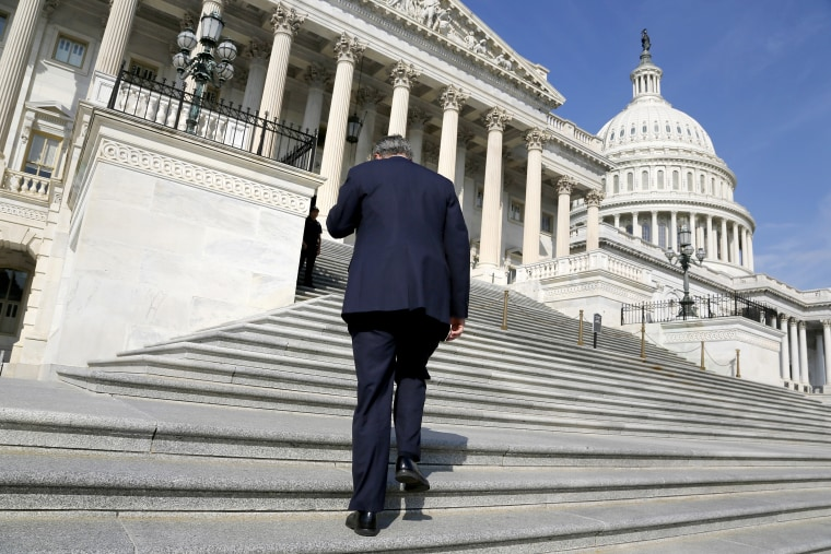 A member of the U.S. House of Representatives talks on the phone as he arrives for a vote at the U.S. Capitol in Washington October 5, 2013.