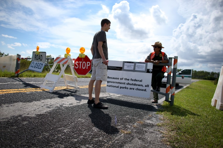 Mirta Maltes a U.S. Park Ranger law enforcement officer speaks with Christoph Zuercher, a tourist from Switzerland, at a road closed sign leading to the Everglades National Park after he discovered the park was closed on October 7, 2013 in Miami, Florida.