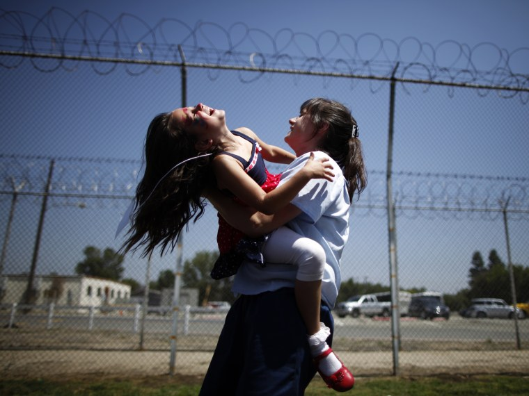 Cori Walters, 32, (R) hugs her daughter Hannah Walters, 6, at California Institute for Women state prison in Chino, California May 5, 2012.