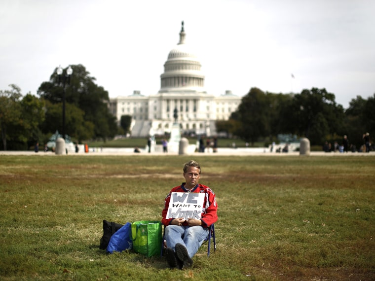 Furloughed Americorps employee Jeffrey Wismer sits alone on the Washington Mall October 8, 2013, as he calls on congress to end the government shut down.