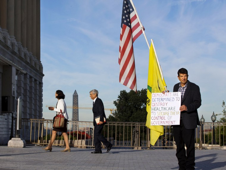A member of the Tea Party holds a sign against Obamacare outside the Senate side of the Capitol in Washington, Wednesday, Sept. 25, 2013.