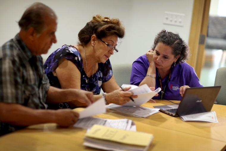 Affordable Care Act navigator Nini Hadwen speaks with Jorge Hernandez and Marta Aguirre as they shop for health insurance.