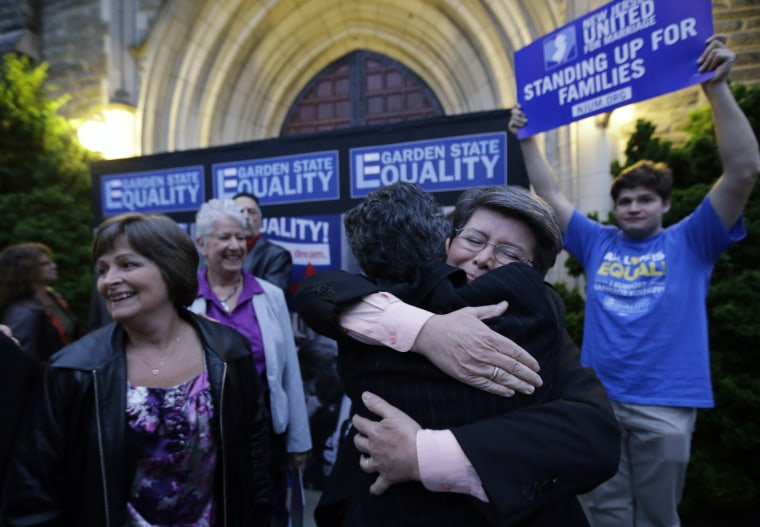 Cindy Meneghin, second from right, hugs her attorney Hayley Gorenberg during a rally at Garden State Equality in Montclair, N.J., after a Superior Court Judge ruled that New Jersey is unconstitutionally denying federal benefits to gay couples and must all