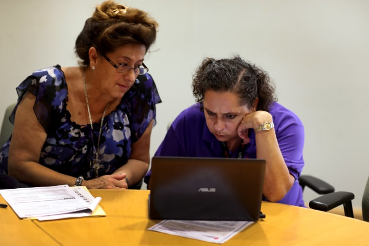 Affordable Care Act navigator Nini Hadwen (R) works with Marta Aguirre as she shops for health insurance during a navigation session put on by the Epilepsy Foundation Florida to help people sign up for health insurance under the Affordable Care Act on Oct