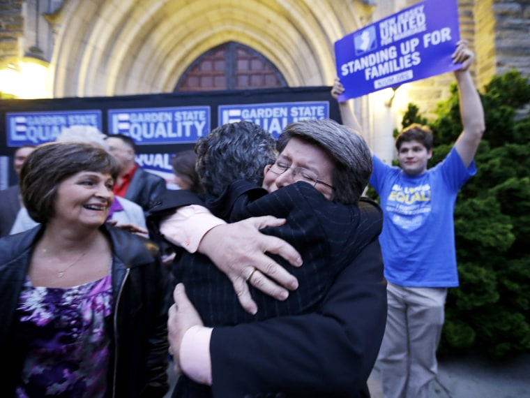 Cindy Meneghin hugs her attorney during a rally at Garden State Equality in Montclair, N.J., hours after same-sex marriages were made legal by a state judge, Friday, Sept. 27, 2013.