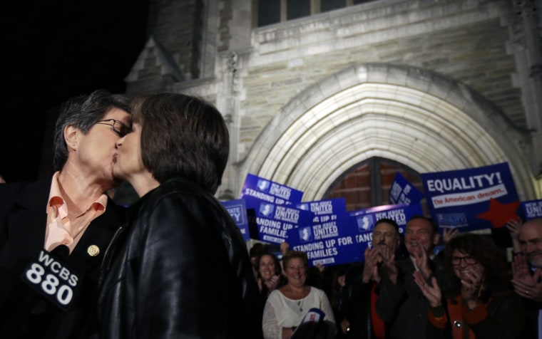 Cindy Meneghin, left, kisses her partner Maureen Kilian, both from Butler, N.J., during a news conference at Garden State Equality in Montclair, N.J.