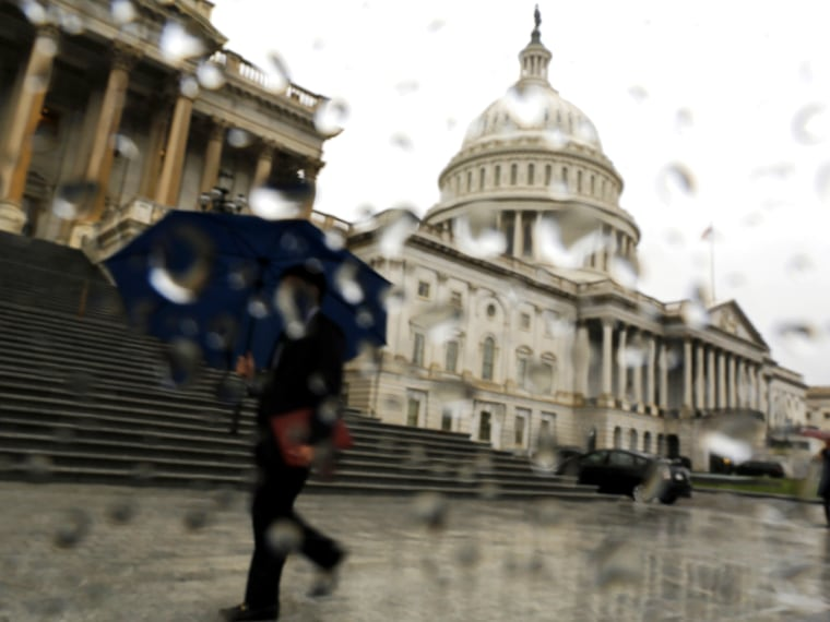 A man with an umbrella walks as it rains at the U.S. Capitol in Washington