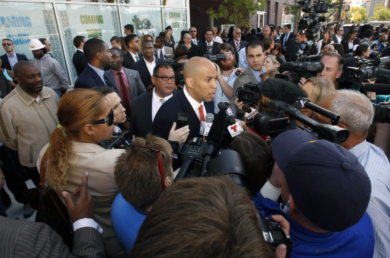 Democratic Newark Mayor and senate candidate Cory Booker, center, is surrounded by media as he answers questions in Newark, N.J. on Wednesday, Sept. 25, 2013, after a ribbon-cutting ceremony for Newark charter schools.
