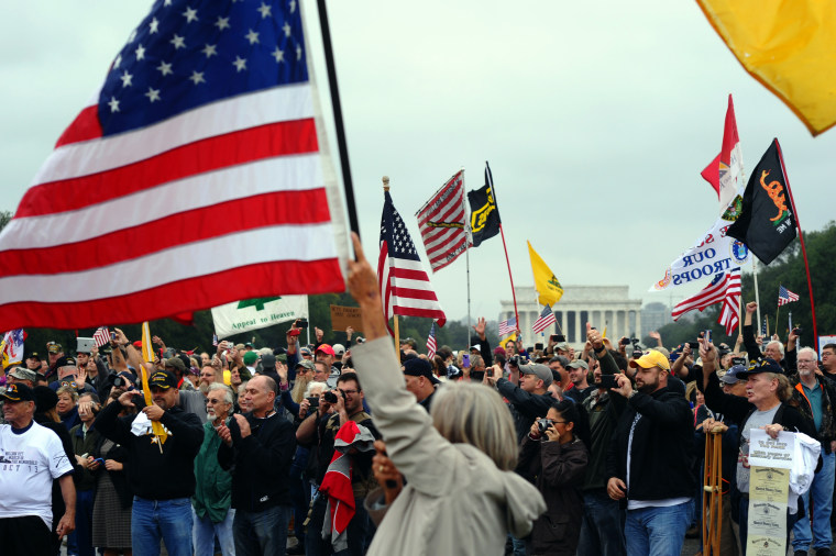 Protesters wave flags during a demonstration at the World War II memorial in Washington, DC, on Oct. 13, 2013 demanding for an end of US federal government shutdown.