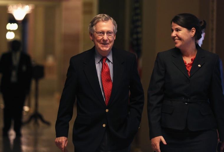 U.S. Minority Leader Senator Mitch McConnell (R-KY) walks towards the Senate Chamber with Secretary of the Minority Laura Dove October 7, 2013